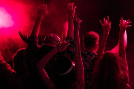 Photo pour Vue arrière des personnes avec les mains levées pendant la fête rave dans la boîte de nuit avec éclairage rose - image libre de droit