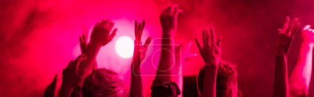 Photo for Panoramic shot of back view of people with raised hands during rave party in nightclub - Royalty Free Image