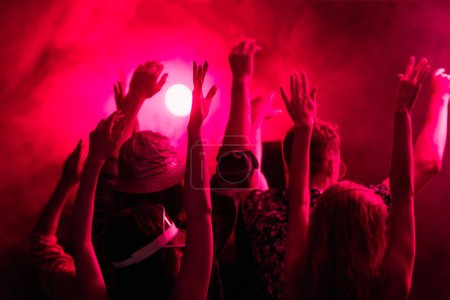 back view of people with raised hands during rave party in nightclub
