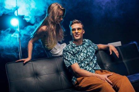 Photo pour Homme et jeune femme assis sur le canapé pendant la fête de rave dans la boîte de nuit - image libre de droit