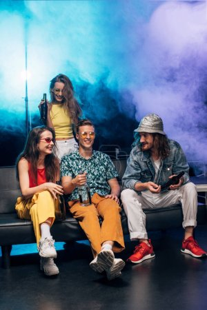 Photo for Young women and men with alcohol sitting on couch in nightclub - Royalty Free Image