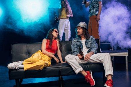 Photo pour Homme avec de l'alcool et belle fille assise sur le canapé dans la boîte de nuit - image libre de droit