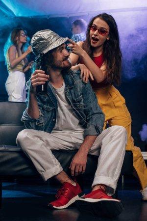 Photo pour Homme avec de l'alcool et fille assis sur le canapé dans la boîte de nuit - image libre de droit