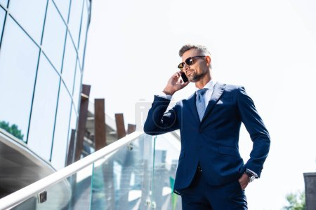 handsome man in suit with hand in pocket talking on smartphone