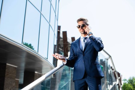 handsome man in suit and glasses talking on smartphone