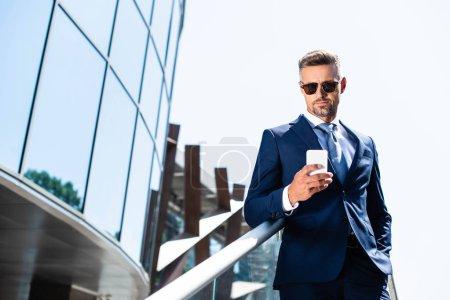 hombre guapo en traje con la mano en el bolsillo usando el teléfono inteligente