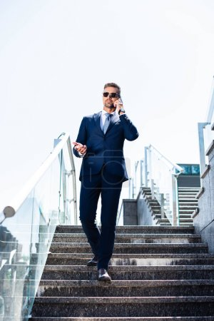 Photo for Handsome man in suit and glasses talking on smartphone - Royalty Free Image