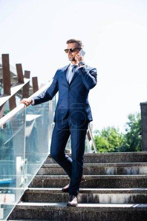 hombre guapo en traje y gafas hablando en el teléfono inteligente