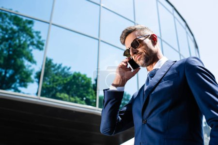 Photo for Low angle view of handsome man in suit and glasses talking on smartphone - Royalty Free Image