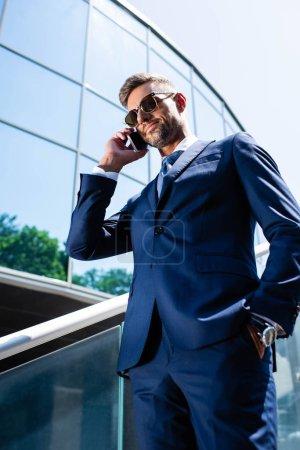 vista de ángulo bajo del hombre guapo en traje y gafas hablando en el teléfono inteligente