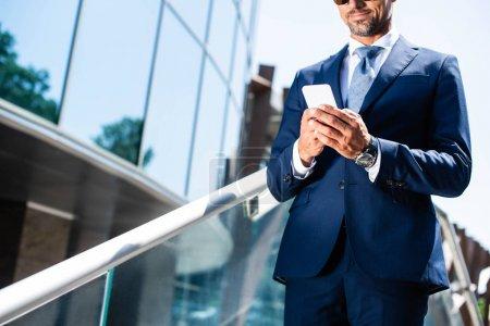 Photo pour Vue recadrée de l'homme en costume à l'aide d'un smartphone extérieur - image libre de droit