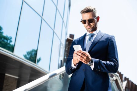 handsome man in suit and glasses using digital device