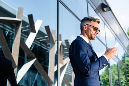 Photo for Side view of handsome man in suit and glasses using smartphone - Royalty Free Image