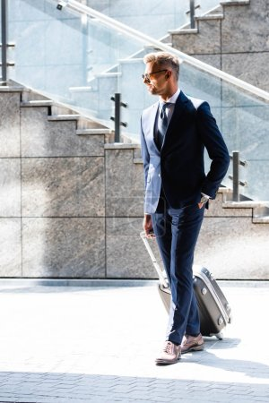 Photo for Handsome man in suit and glasses with hand in pocket holding suitcase - Royalty Free Image