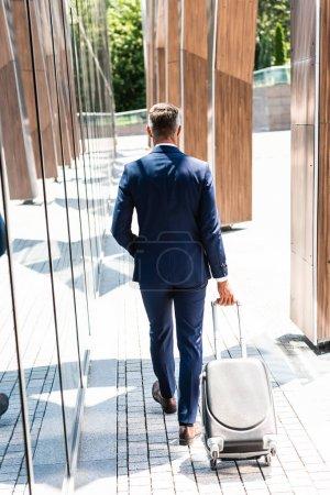 vue arrière de l'homme d'affaires en costume tenant une valise à l'extérieur