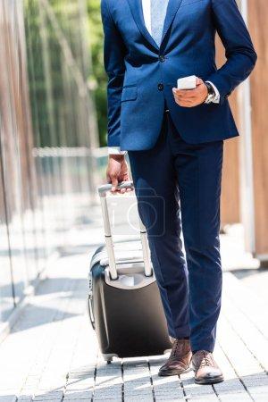 Foto de Vista recortada del hombre de negocios en traje sosteniendo la maleta y el teléfono inteligente - Imagen libre de derechos