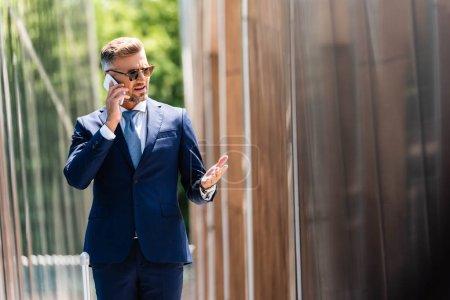 hombre de negocios guapo en traje y gafas hablando en smartphone