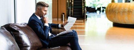 Foto de Plano panorámico de hombre de negocios guapo en traje mirando los papeles - Imagen libre de derechos