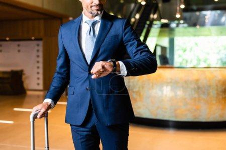 recortado vista de hombre de negocios en traje mirando reloj