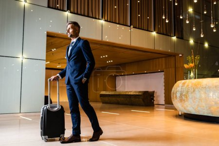 Photo for Handsome businessman in suit with hand in pocket holding suitcase - Royalty Free Image