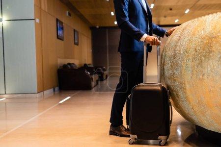 Photo pour Vue recadrée de l'homme d'affaires dans la valise de fixation de procès dans l'hôtel - image libre de droit