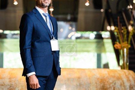 Photo pour Vue recadrée de l'homme d'affaires en costume avec badge à l'hôtel - image libre de droit