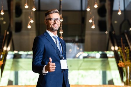 Photo for Handsome businessman in suit and glasses showing thumb up - Royalty Free Image