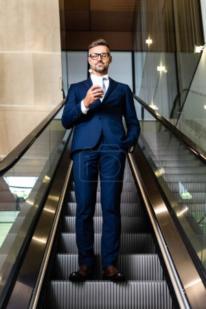 handsome businessman in suit and glasses with hand in pocket using smartphone