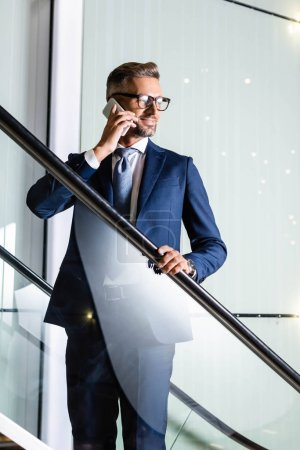 handsome businessman in suit and glasses talking on smartphone