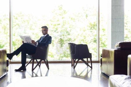 Photo pour Bel homme d'affaires en costume assis sur un fauteuil et lisant un journal - image libre de droit