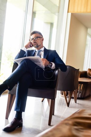 Photo pour Handsome businessman in suit and glasses holding newspaper and looking away - image libre de droit