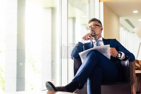 Photo for Handsome businessman in suit and glasses holding newspaper and looking away - Royalty Free Image