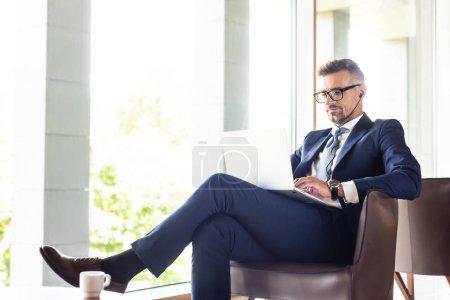 hombre de negocios guapo en traje y gafas con auriculares usando el ordenador portátil