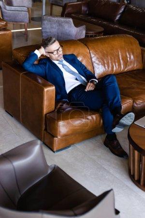Photo pour Homme d'affaires beau dans le procès et les glaces s'asseyant sur le sofa - image libre de droit