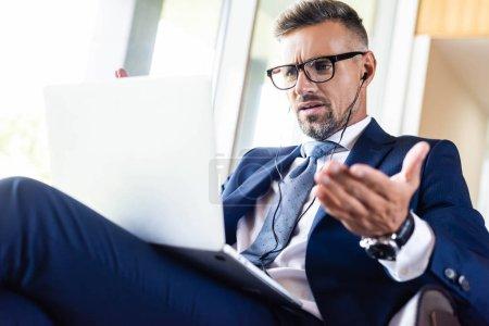 Photo pour Vue bas d'angle de bel homme d'affaires dans le procès et les glaces utilisant l'ordinateur portatif - image libre de droit