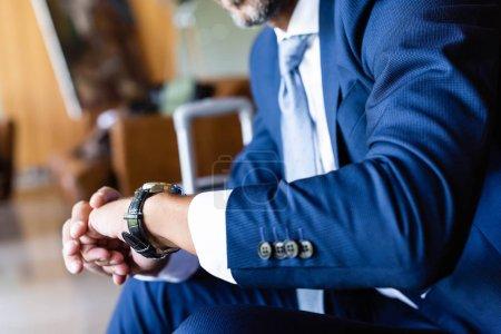 Photo pour Vue recadrée de l'homme en tenue de cérémonie en regardant la montre - image libre de droit
