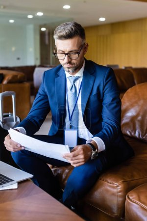 Photo for Handsome businessman in suit and glasses looking at papers - Royalty Free Image