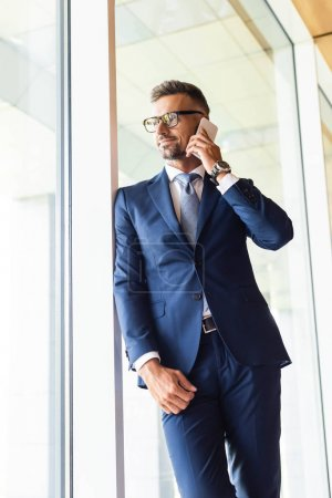 Photo for Handsome businessman in suit and glasses talking on smartphone - Royalty Free Image