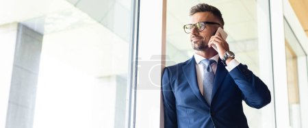 Photo for Panoramic shot of handsome businessman in suit and glasses talking on smartphone - Royalty Free Image