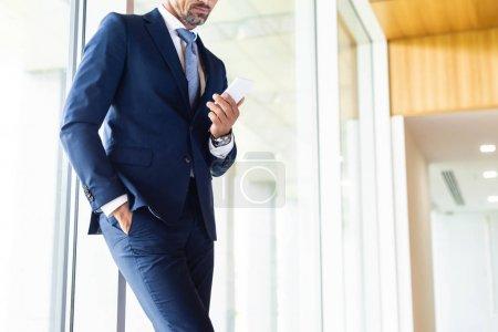 Photo pour Vue recadrée de l'homme d'affaires en costume avec la main dans la poche en utilisant smartphone - image libre de droit