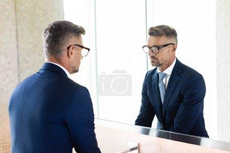 Photo pour Homme d'affaires beau dans l'usure formelle et les glaces regardant le miroir - image libre de droit