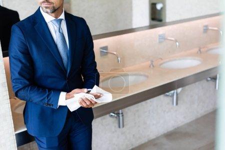 Photo pour Vue recadrée de l'homme d'affaires dans l'usure formelle essuyant des mains - image libre de droit