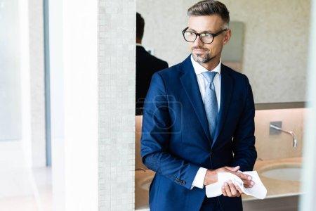 Photo pour Bel homme d'affaires dans l'usure formelle et les lunettes essuyant des mains - image libre de droit