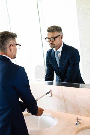 Photo pour Beau homme d'affaires dans l'usure formelle et les lunettes se laver les mains - image libre de droit