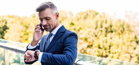 Photo pour Tir panoramique de l'homme d'affaires beau dans l'usure formelle parlant sur le smartphone - image libre de droit