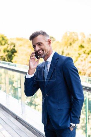 hombre de negocios guapo y sonriente en ropa formal hablando en el teléfono inteligente