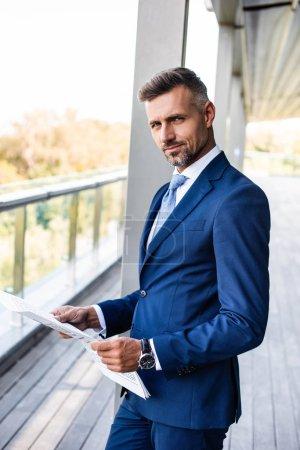 guapo y confiado hombre de negocios en ropa formal celebración de periódico