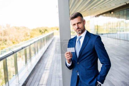 guapo hombre de negocios en ropa formal con la mano en el bolsillo celebración de la tarjeta en blanco