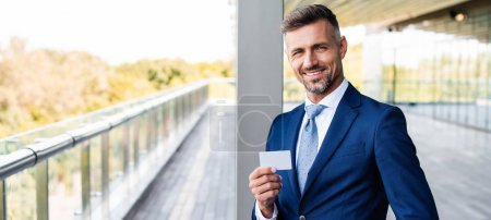 panoramic shot of handsome businessman in formal wear holding blank card