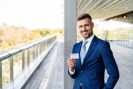 Photo for Handsome businessman in formal wear with hand in pocket holding blank card - Royalty Free Image
